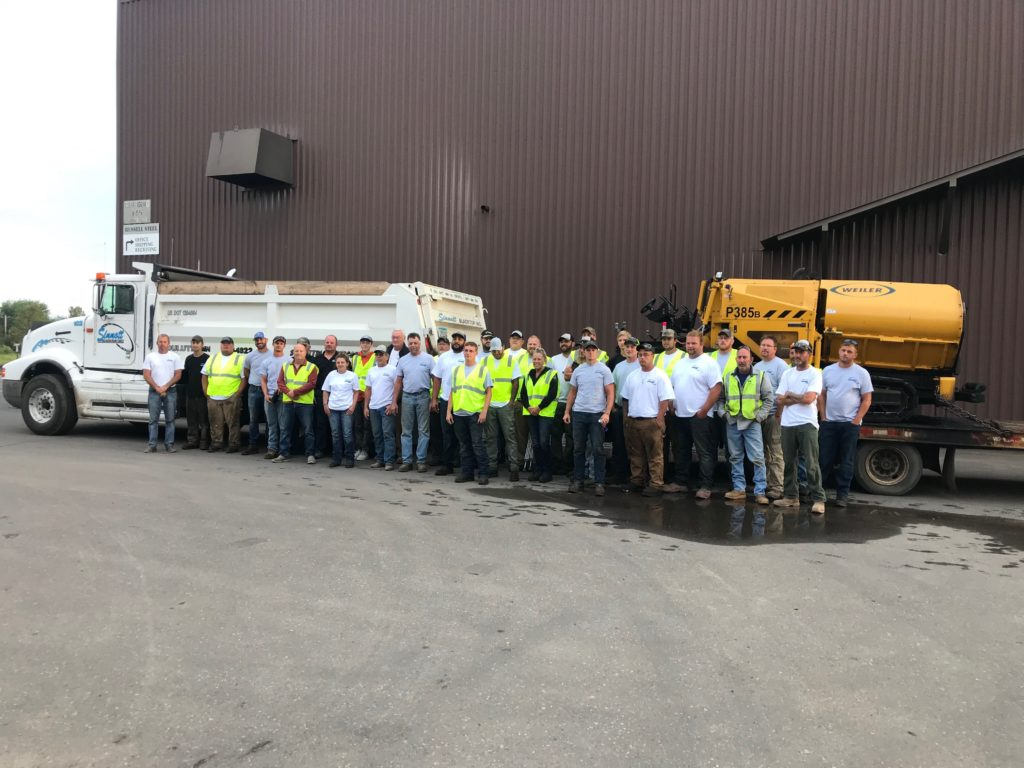 Sinnott Blacktop team members standing in front of trucks and equipment outside